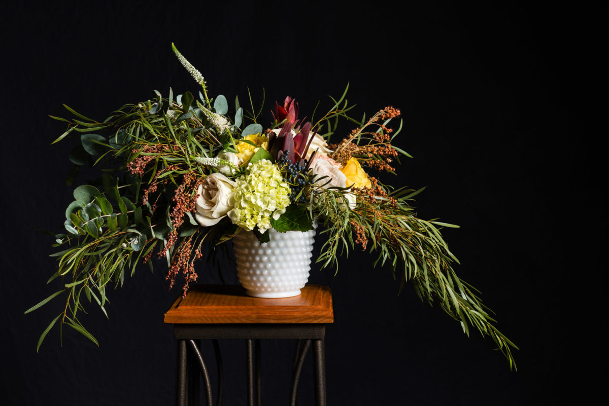 Beautiful flower arrangement in low vase on stand