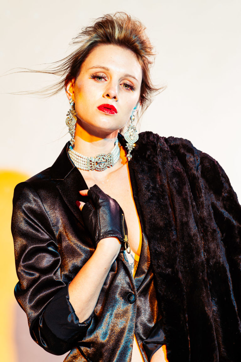 Fashion photography with blue and yellow colored gels of young woman in black satin jacket and jewelry