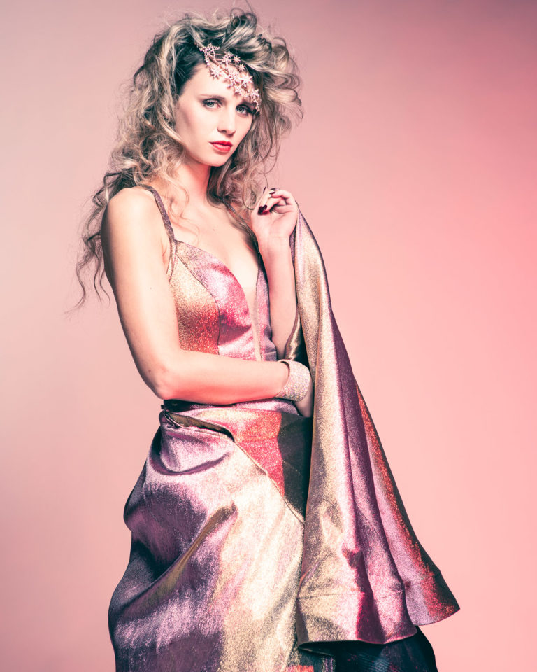Fashion photography with colored gels of young woman in irridescent party gown