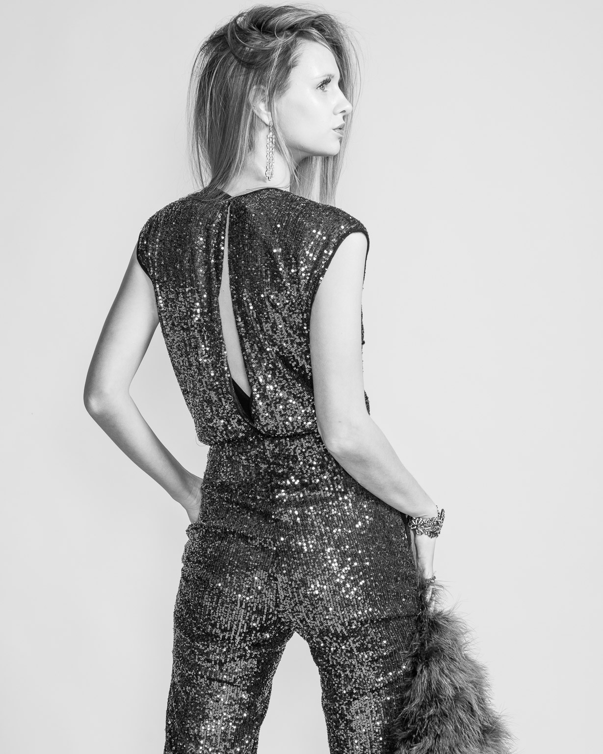 Fashion photography of young woman in stylish sequined jumpsuit standing in fashion pose.
