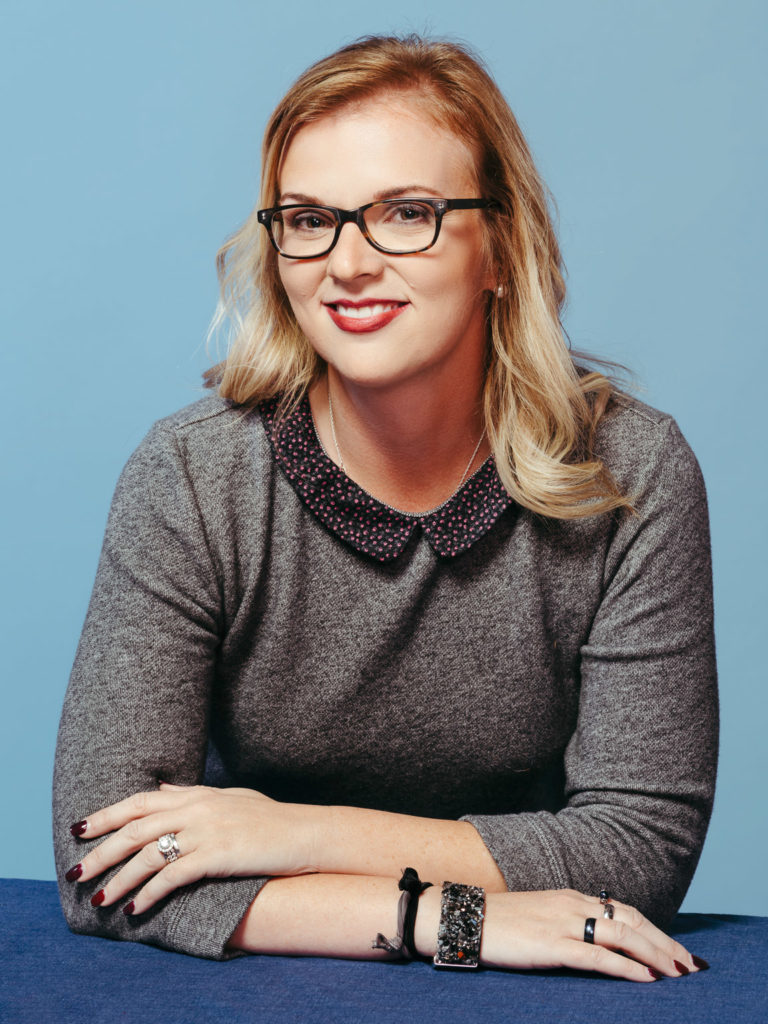 Headshot of woman in glasses on blue background