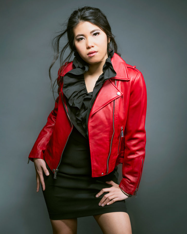 Young stylish Asian woman in short black dress and bright red leather jacket