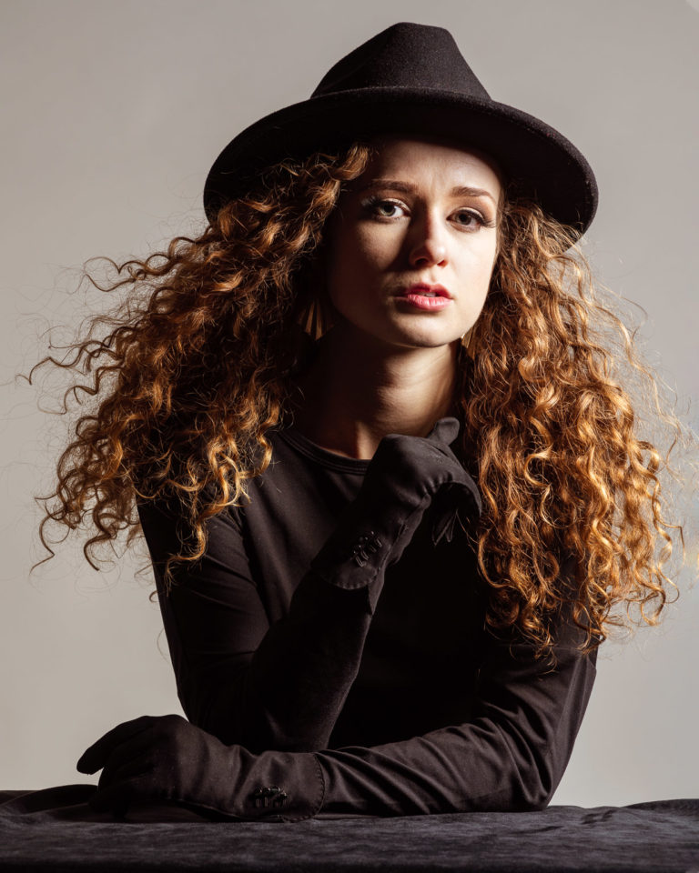 Dramatic lighting for portrait of model in all black with black hat