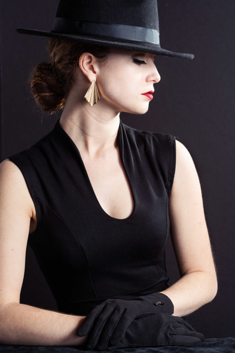 Portrait of stylish model in short black dress and black hat on black background