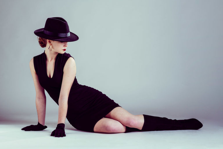 Portrait of stylish model in short black dress and black hat on light grey background