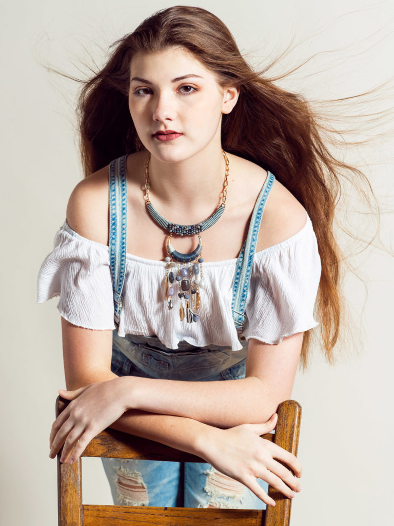 Model with long brown hair in off-shoulder shirt and overalls leaning on chair on studio set