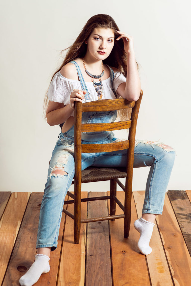 Model with long brown hair in off-shoulder shirt and overalls sitting in chair on studio set