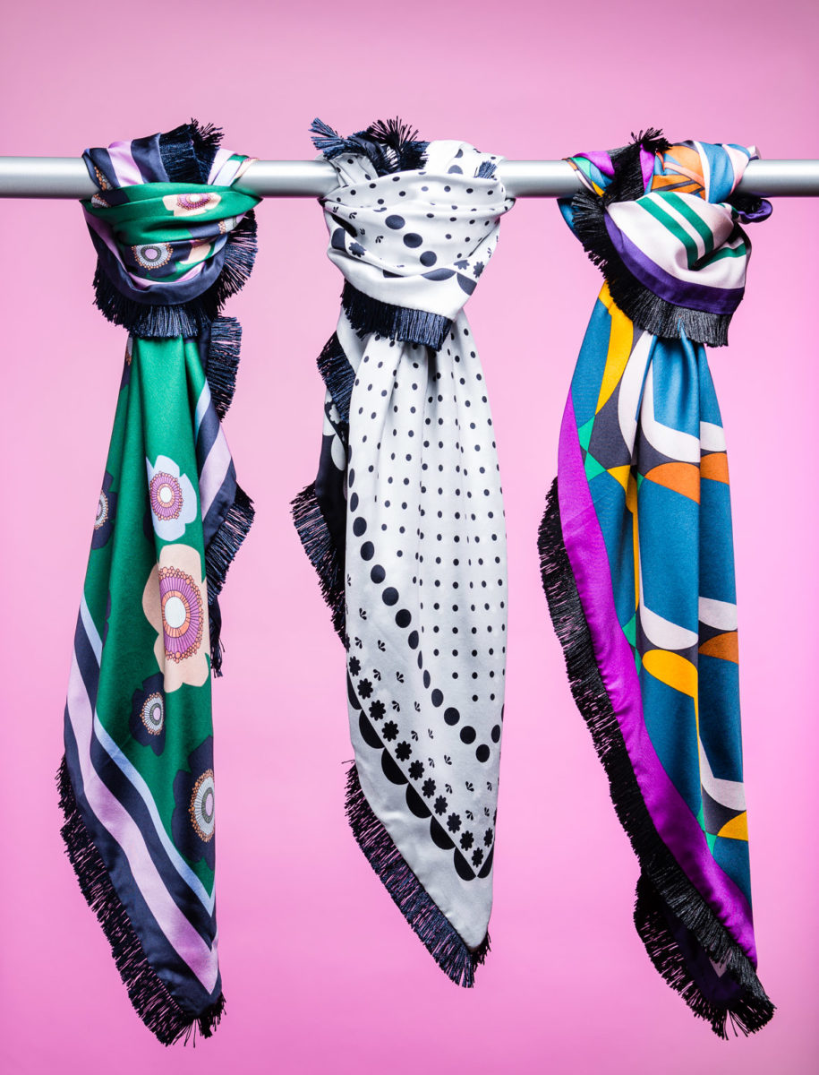 Product photography of three scarves on colored background