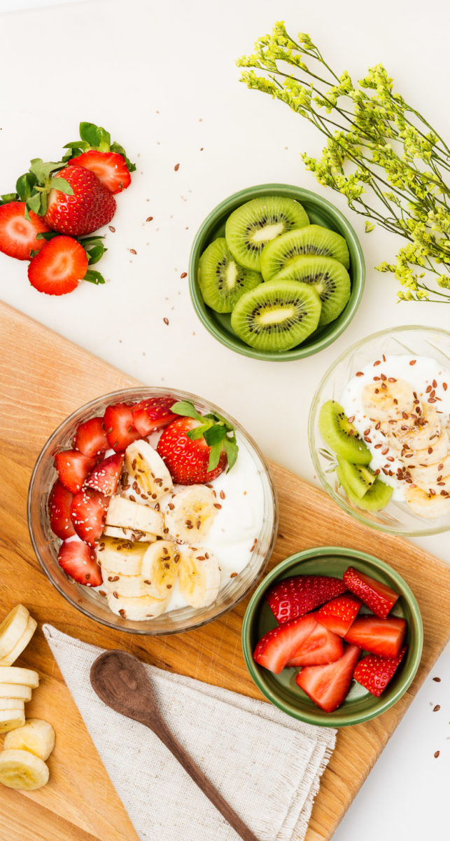 Food photography of yogurt strawberries bannanas and kiwis